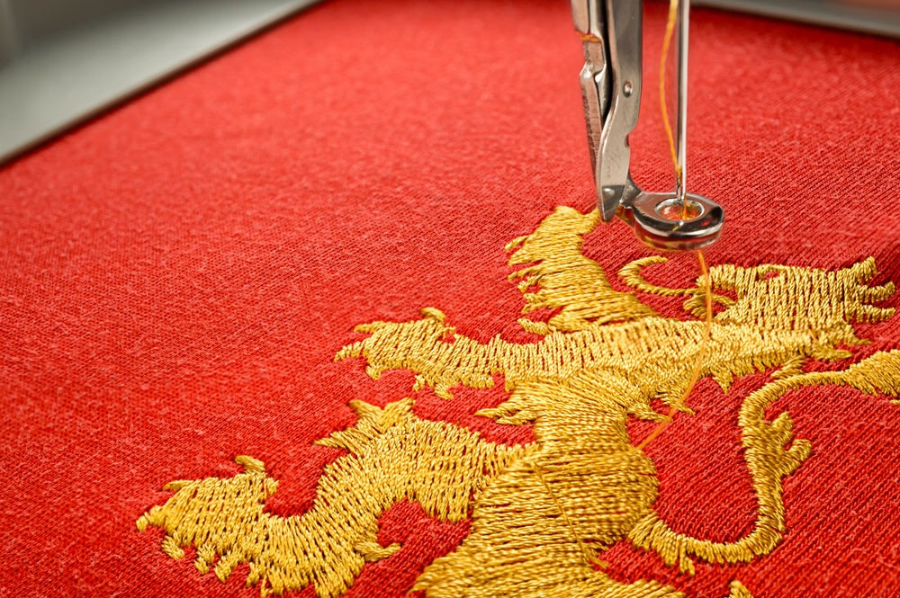 Close up picture embroidery design gold lion on red fabric